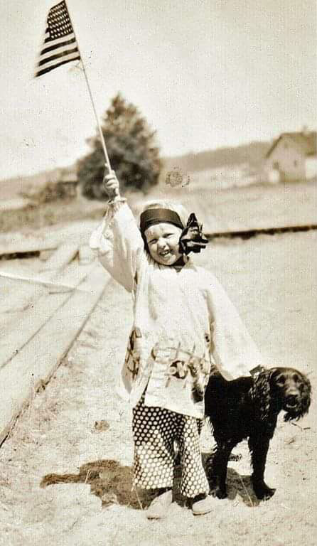 A sepia photo of a little girl on a beach, with a big bow in her hair, in the 1930s, waving an American flag overhead with her right hand, and holding the collar of a black spaniel with her left hand.